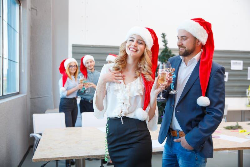 Comemorando colegas em chapéus de Santa no fundo do escritório Conceito do feriado do Natal Copie o espaço foto de stock royalty free