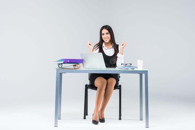 Comemorando a mulher de negócios que senta-se na tabela com o laptop isolado no fundo branco foto de stock