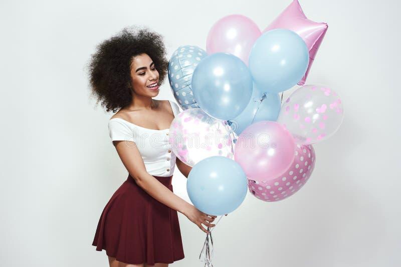 Comemorando o aniversário Mulher afro-americana lindo com o cabelo encaracolado que guarda balões coloridos ao estar contra fotos de stock royalty free