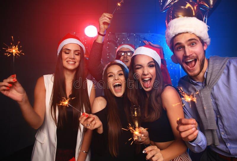 Comemorando o ano novo junto Grupo de jovens bonitos nos chapéus de Santa que jogam confetes coloridos, olhando feliz fotos de stock