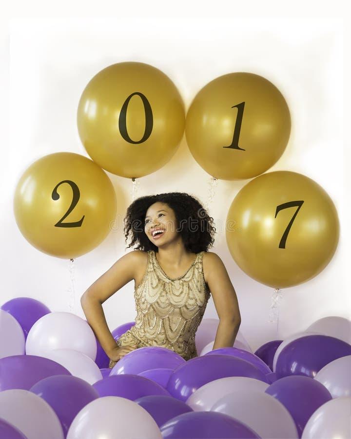 Comemore boas épocas! A jovem mulher de riso atrativa comemora com balões imagem de stock