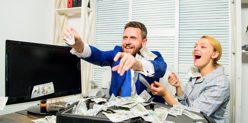 Comemore o lucro Pontas fáceis do negócio do lucro Os colegas felizes alegres do homem e da mulher jogam acima cédulas do dólar l foto de stock royalty free