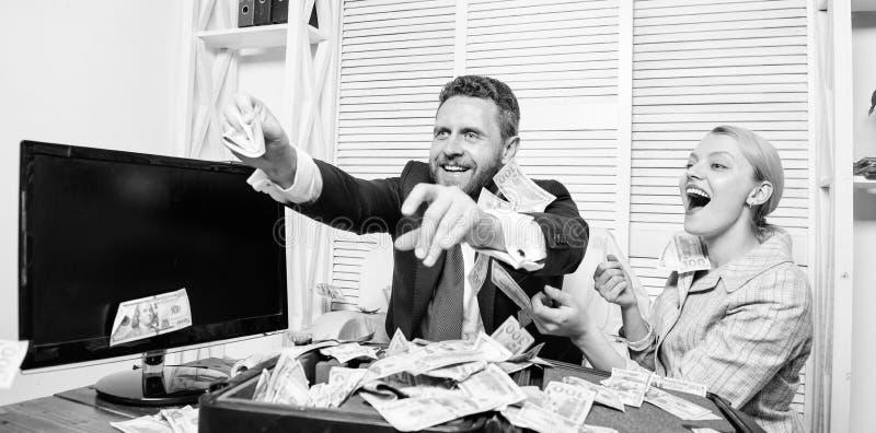Comemore o lucro Pontas f?ceis do neg?cio do lucro Os colegas felizes alegres do homem e da mulher jogam acima c?dulas do d?lar l imagem de stock
