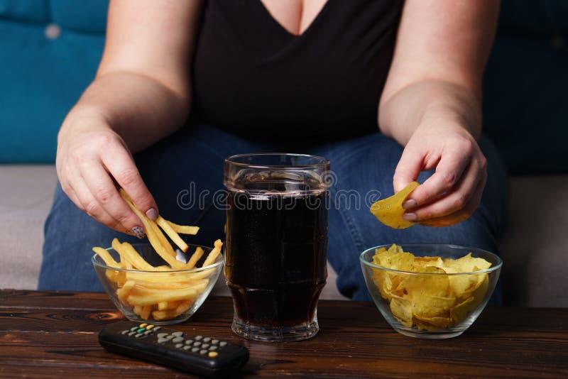 Comendo demais, estilo de vida sedentariamente, hábitos maus imagens de stock royalty free