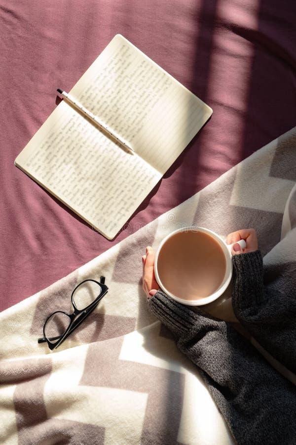 Comendo o café e leitura na cama na manhã ensolarada preguiçosa Ciew superior fotografia de stock royalty free
