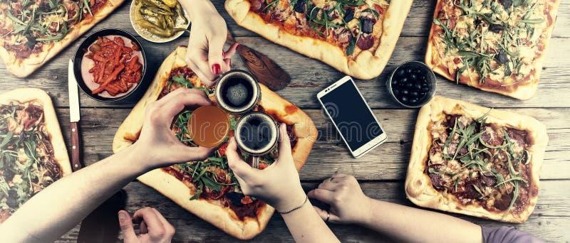 Comendo o conceito Apreciando o jantar com amigos, ideia superior do grupo de pessoas que tem o jantar junto ao sentar-se no wood imagem de stock