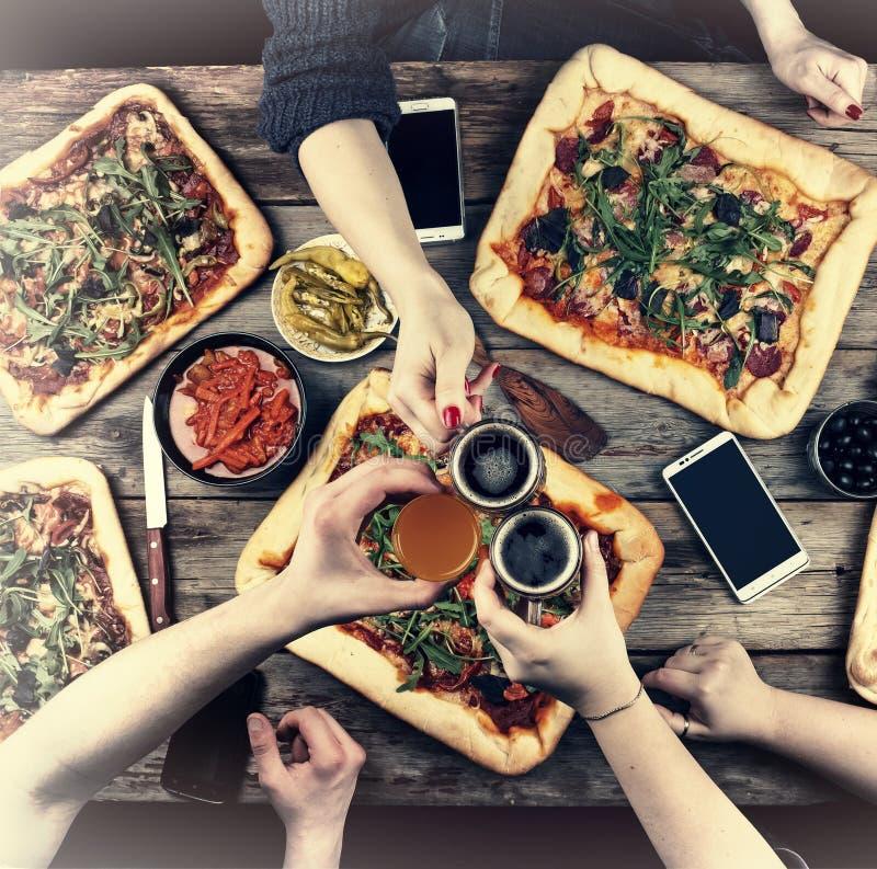 Comendo o conceito Apreciando o jantar com amigos, ideia superior do grupo de pessoas que tem o jantar junto ao sentar-se no wood fotografia de stock