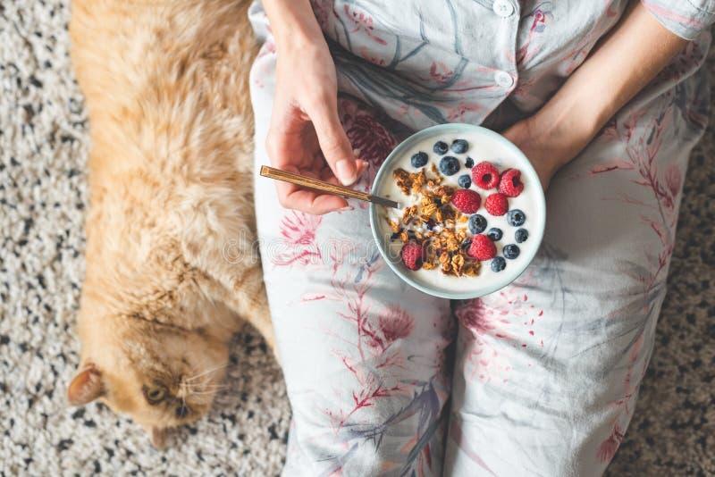Comendo o iogurte com granola e bagas Café da manhã saudável comer fêmea fotografia de stock