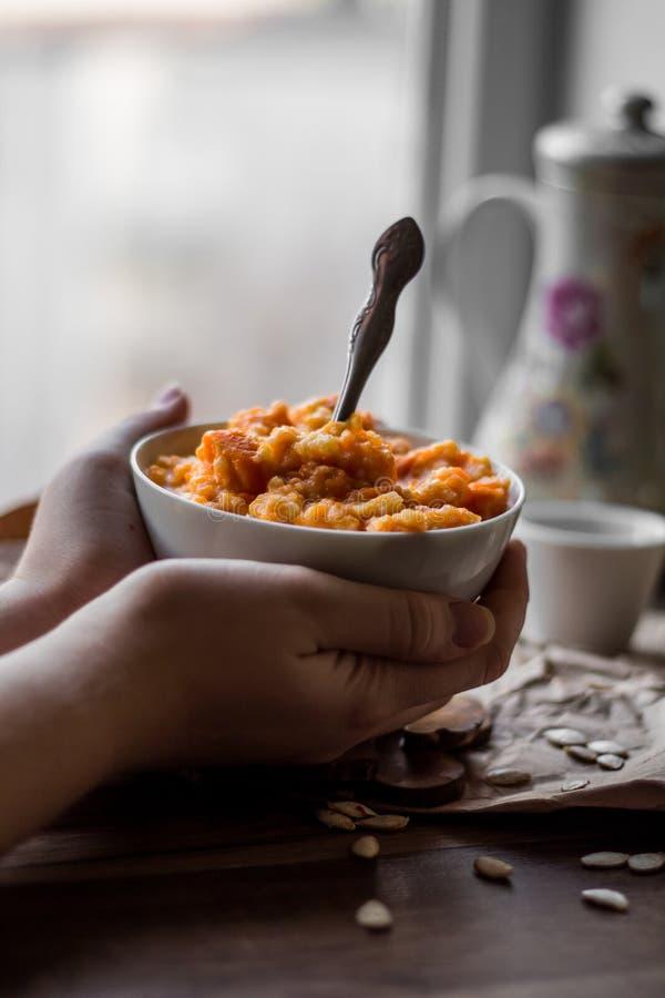 Comendo o papa de aveia do painço da abóbora com leite, mãos, café da manhã imagens de stock royalty free