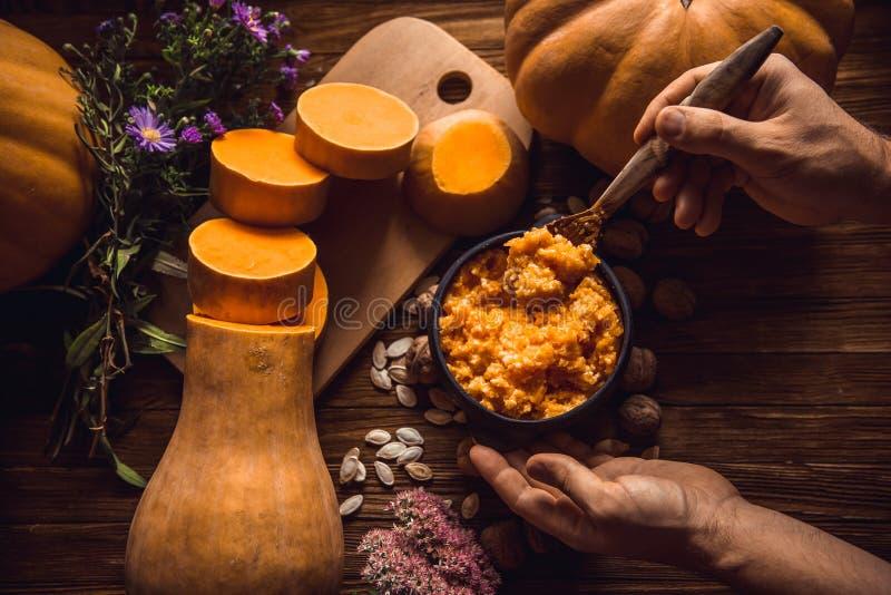 Comendo o papa de aveia do painço da abóbora com leite, mãos, café da manhã em um fundo de madeira imagens de stock royalty free