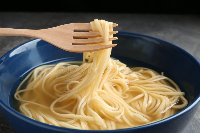 Comendo o prato do macarronete com a forquilha na tabela foto de stock royalty free