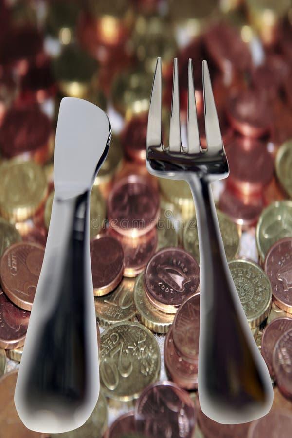 Comendo para fora a faca e a forquilha isoladas no dinheiro fotografia de stock