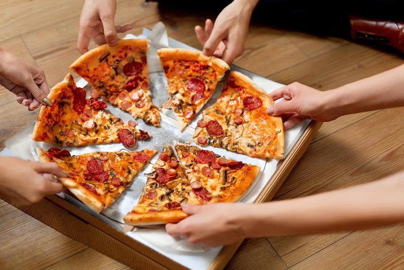 Comendo a pizza Grupo de amigos que compartilham da pizza Fast food, lazer foto de stock