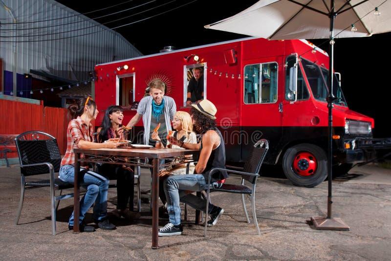 Comendo a pizza perto do caminhão do alimento foto de stock