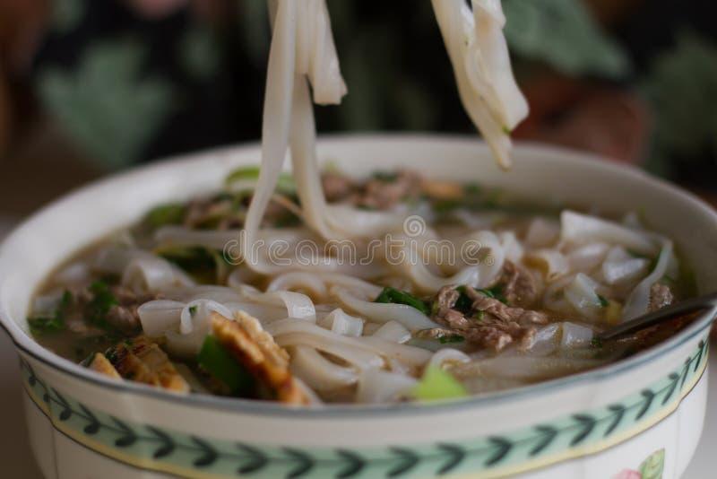 Comendo uma bacia de sopa de macarronete vietnamiana Pho da carne BO fotografia de stock royalty free