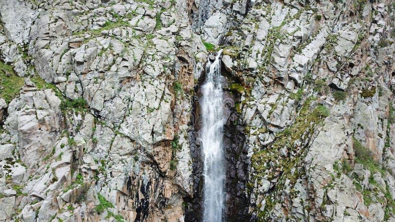 Comenzó la caída de la cascada El top de la cascada en las rocas con la hierba verde fotos de archivo