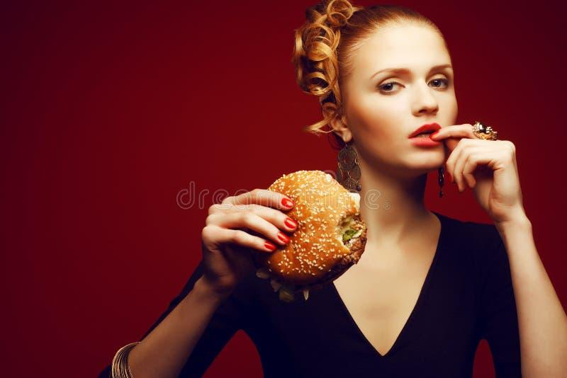Comer insalubre Conceito da comida lixo Mulher que come o hamburguer imagem de stock