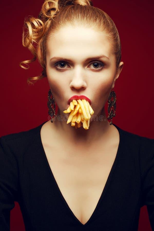 Comer insalubre Conceito da comida lixo Retrato dos Arty da mulher com fritadas foto de stock