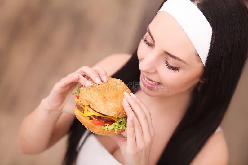 Comer insalubre Conceito da comida lixo Retrato da jovem mulher elegante que guarda o hamburguer e que levanta sobre o fundo de m imagem de stock