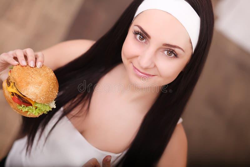 Comer insalubre Conceito da comida lixo Retrato da jovem mulher elegante que guarda o hamburguer e que levanta sobre o fundo de m imagens de stock royalty free