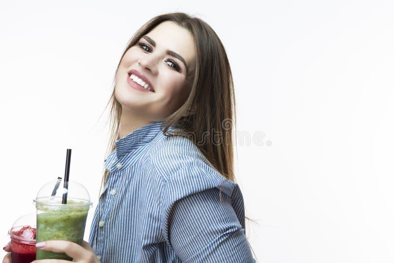 Comer saudável do alimento Mulher caucasiano feliz que bebe com o batido vegetal da desintoxicação verde e vermelha Levantamento  foto de stock
