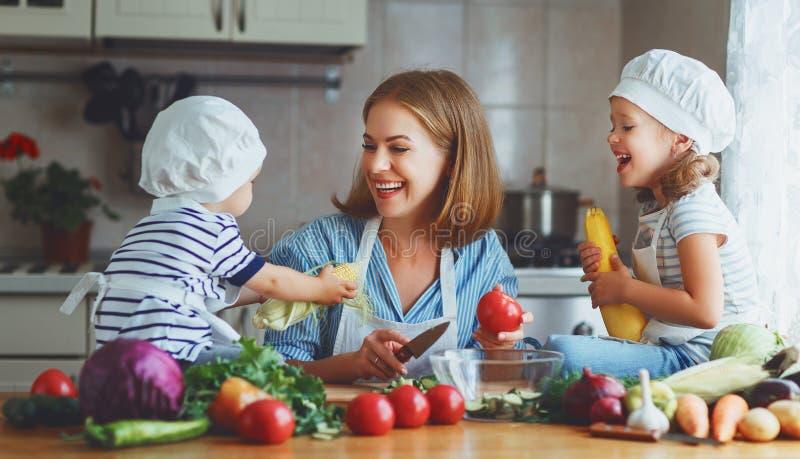 Comer saudável A mãe e as crianças felizes da família preparam a salada vegetal foto de stock
