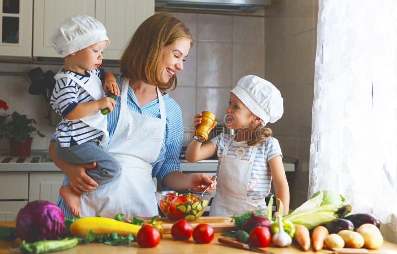 Comer saudável A mãe e as crianças felizes da família preparam a salada vegetal foto de stock royalty free