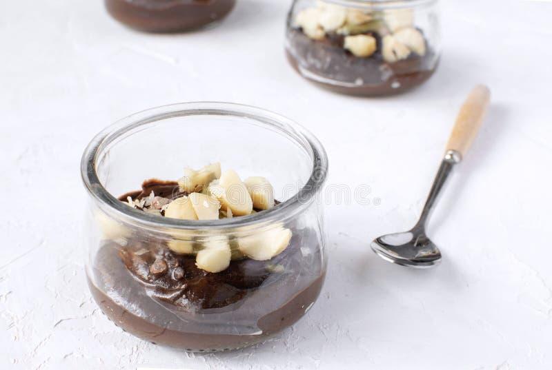 Comer saudável - pudim de chocolate do vegetariano feito do abacate no frasco de vidro com as porcas de macadâmia na parte superi fotos de stock
