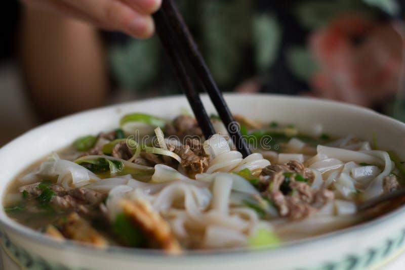 comer uma bacia da sopa de macarronete vietnamiana Pho da carne BO com costeleta cola imagem de stock