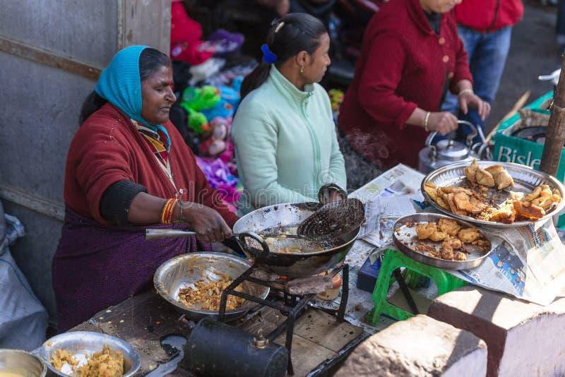 Comerciante de mujer indio que vende el plátano frito en el mercado cerca de Tiger Hill en invierno en Darjeeling, la India fotografía de archivo