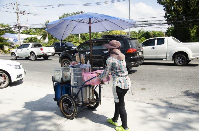 Comerciante de mujer tailandés que empuja el coche del carro para el helado local de coco de la venta imagen de archivo