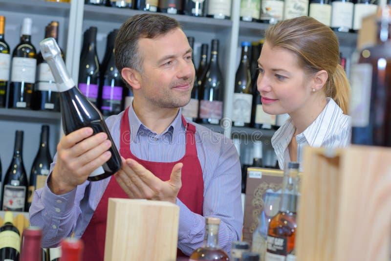 Comerciante de vinho que recomenda o cliente fotos de stock