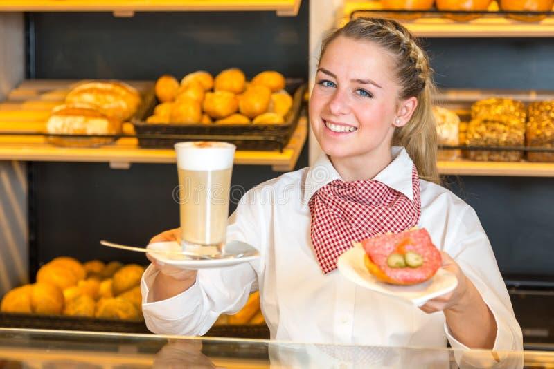 Comerciante en la panadería o la tienda del panadero que presenta el café y el bocadillo imagen de archivo libre de regalías