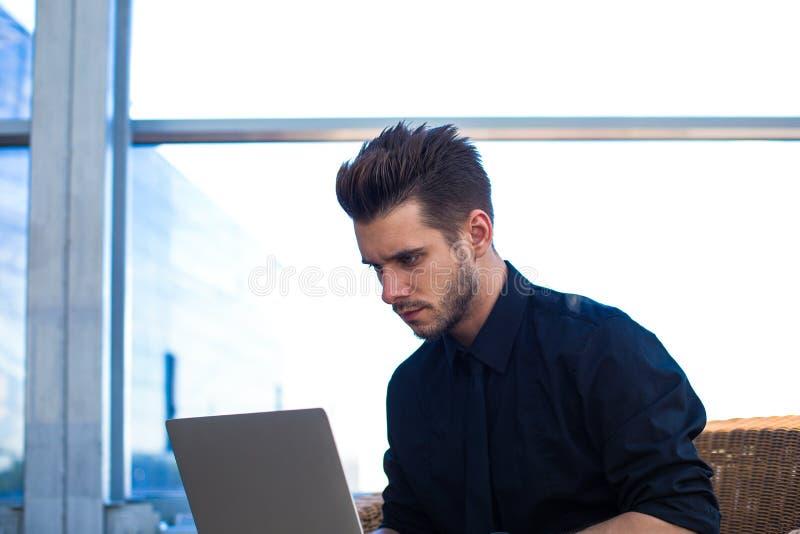 Comerciante profesional del hombre que trabaja en Internet vía el ordenador portátil, sentándose en interior de la oficina imagenes de archivo