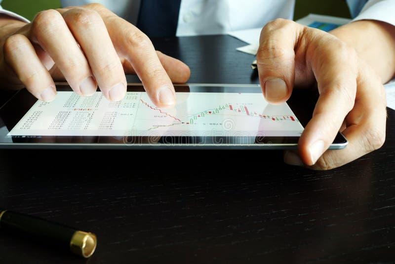 Comerciante que guarda a tabuleta com gráfico do mercado de valores de ação foto de stock royalty free
