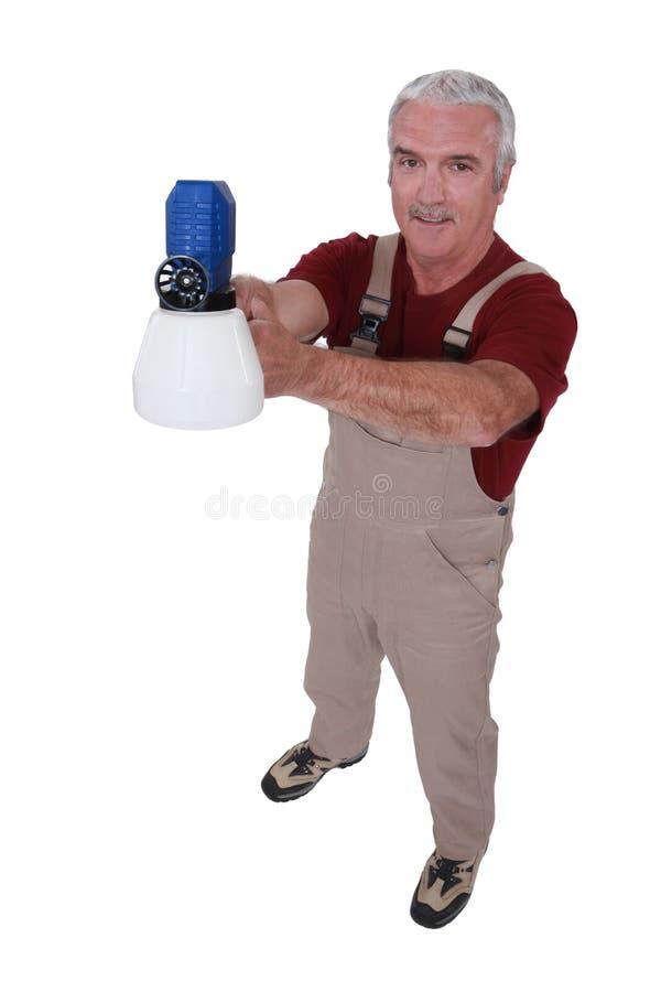Comerciante que sostiene un arma de espray imagen de archivo