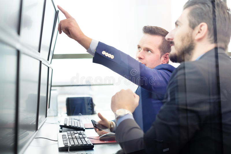 Comerciantes comunes que miran las pantallas de ordenador imagen de archivo