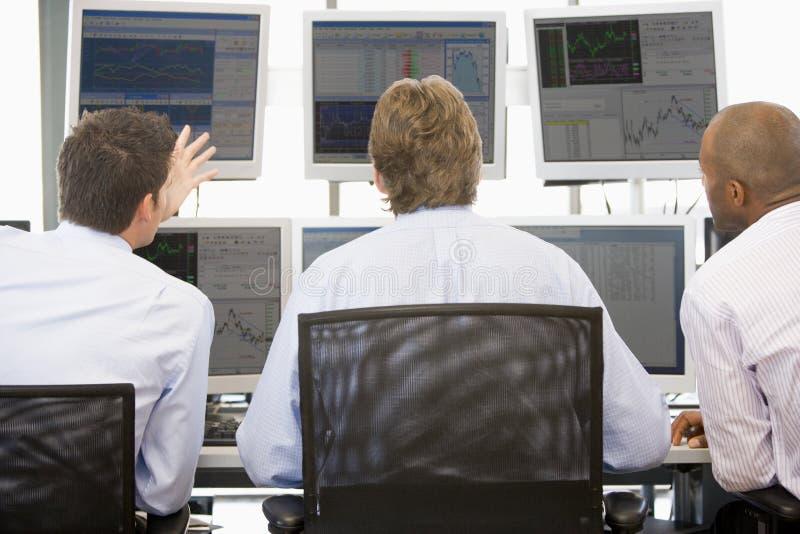 Comerciantes conservados em estoque que vêem monitores fotografia de stock