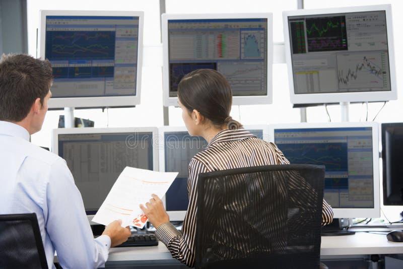 Comerciantes conservados em estoque que vêem monitores fotos de stock