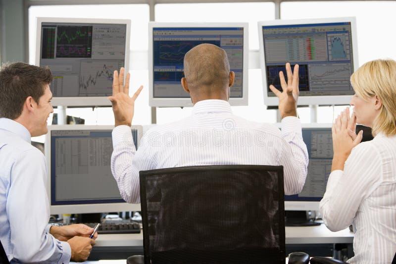 Comerciantes conservados em estoque que vêem monitores imagens de stock