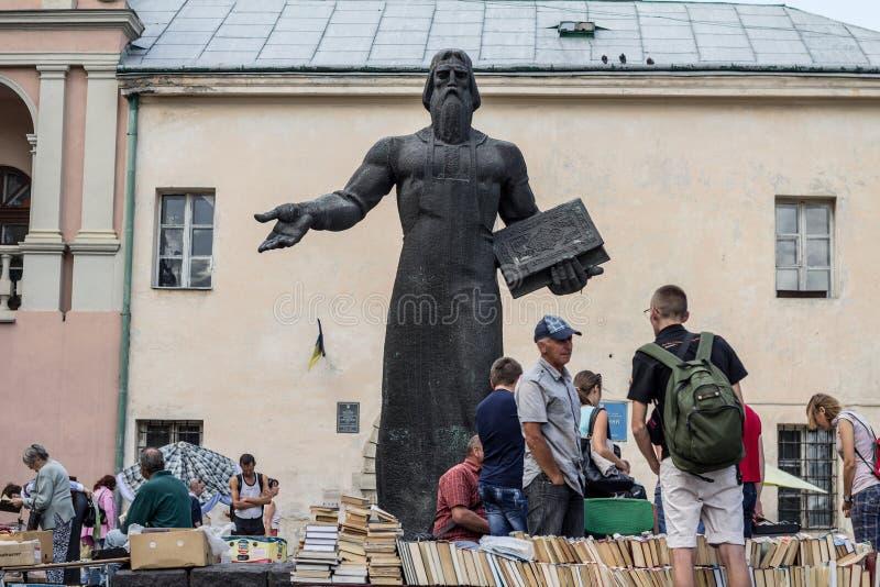 Comerciantes usados do livro que vendem livros usados na frente do monumento a Ivan Fedorov, guardando-se um livro, durante o mer fotos de stock royalty free