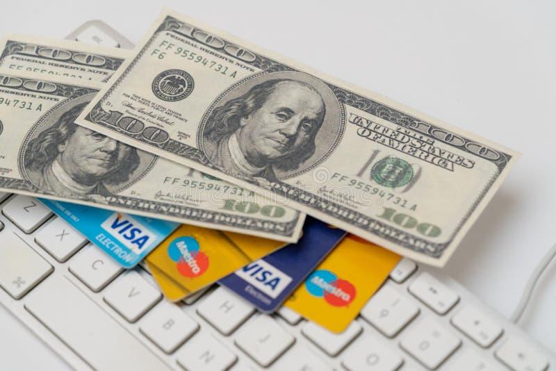 Comercio, comercio electrónico, crédito y tarjetas de débito en línea con dólares y un teclado fotografía de archivo