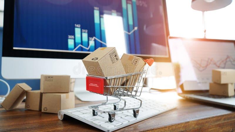 Comercio electr?nico Cajas de papel en carro de la compra y tarjeta de crédito en el teclado y gráfico del desarrollo económico d fotos de archivo libres de regalías