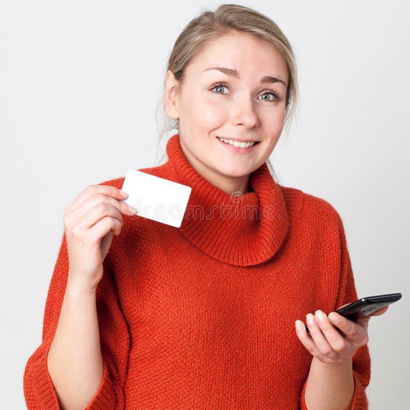 Comercio móvil para la muchacha sonriente que hace la transacción en línea imagen de archivo