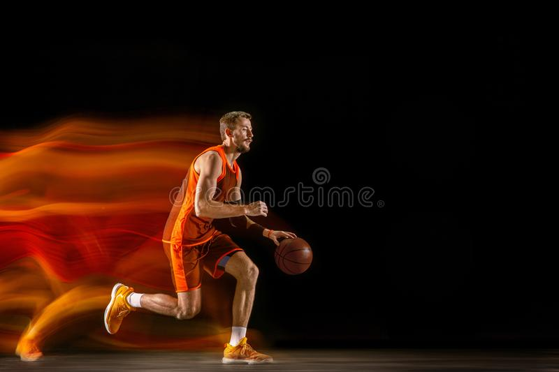 Young caucasian basketball player against dark background in mixed light stock photography