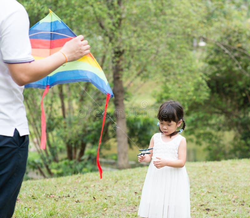 Cometa asiática del vuelo de la familia en el parque foto de archivo libre de regalías