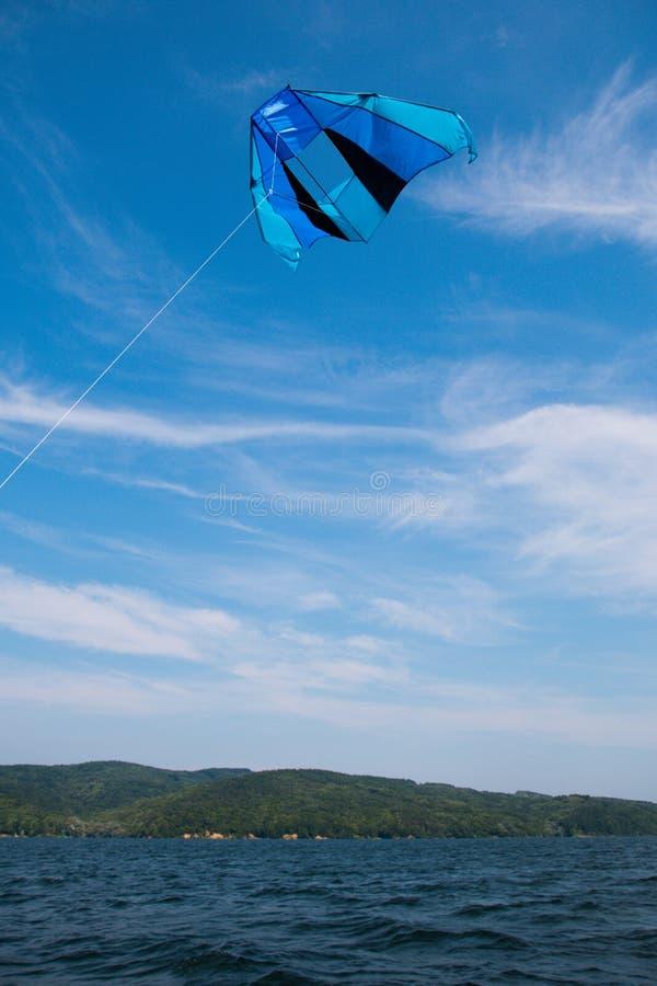 Cometa azul en el cielo azul sobre el agua imagenes de archivo