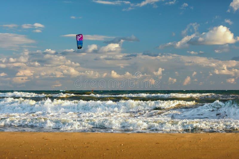 Cometa de los paseos de Kitesurfer a través de ondas que practican surf del mar tempestuoso en la playa arenosa en la puesta del  imagen de archivo libre de regalías
