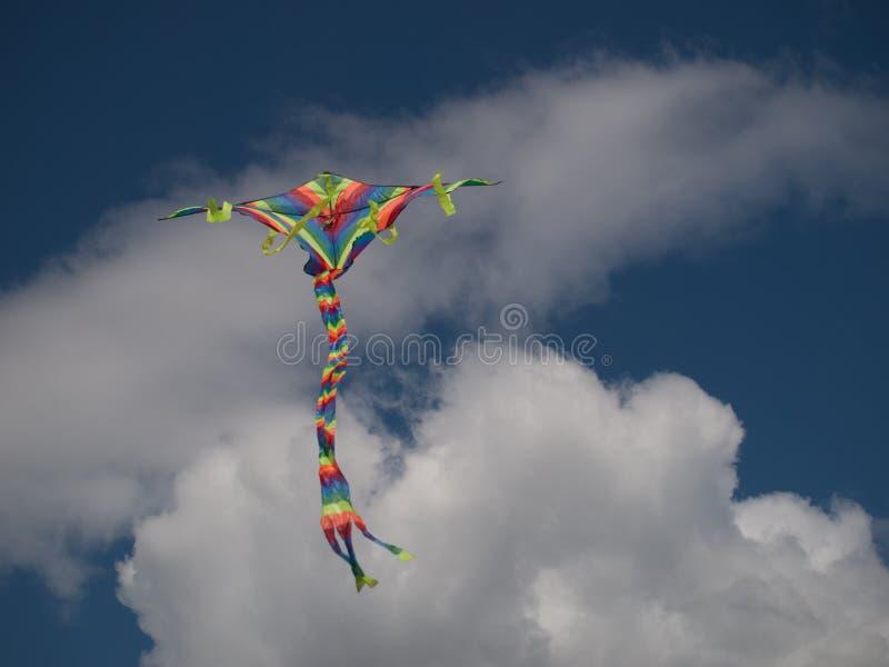 Cometa multicolora contra las nubes blancas y el cielo azul fotos de archivo