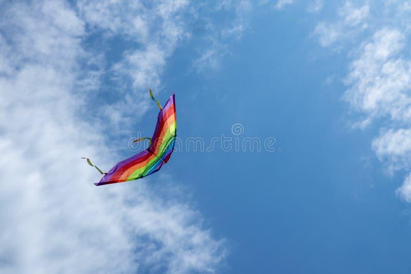 Cometa multicolora en el fondo del cielo azul con las nubes imágenes de archivo libres de regalías